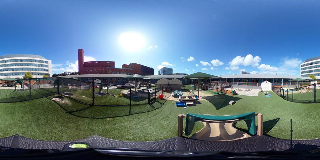 An expansive play area with umbrellas, a sandpit, climbing equipment and toys