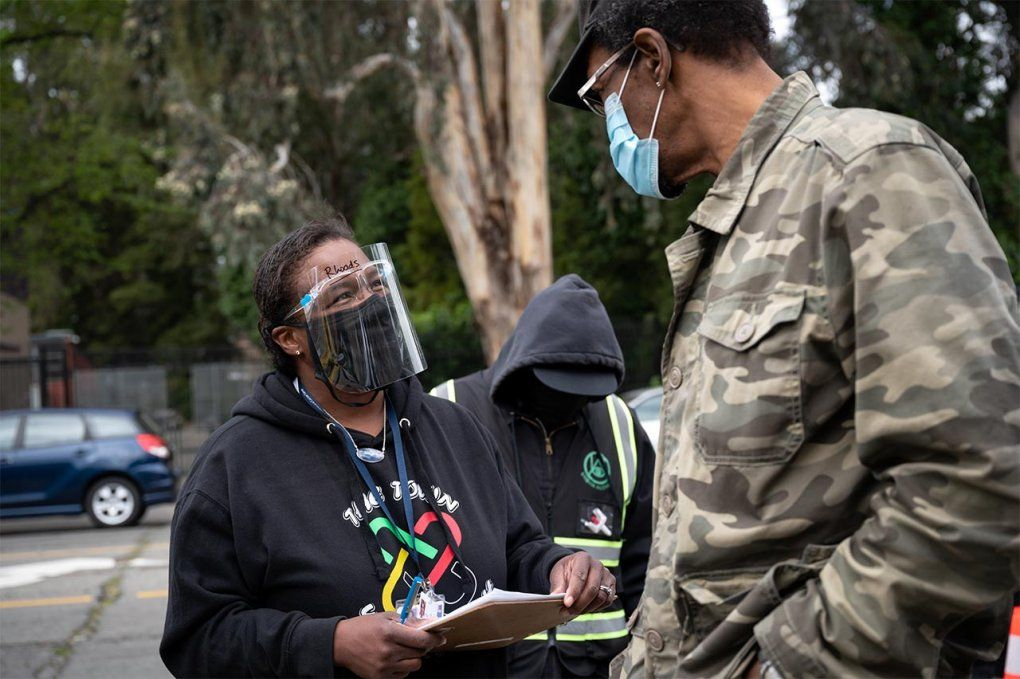 Photo of Kim Rhoads in a face mask and face shield talking to a man at a vaccine clinic.