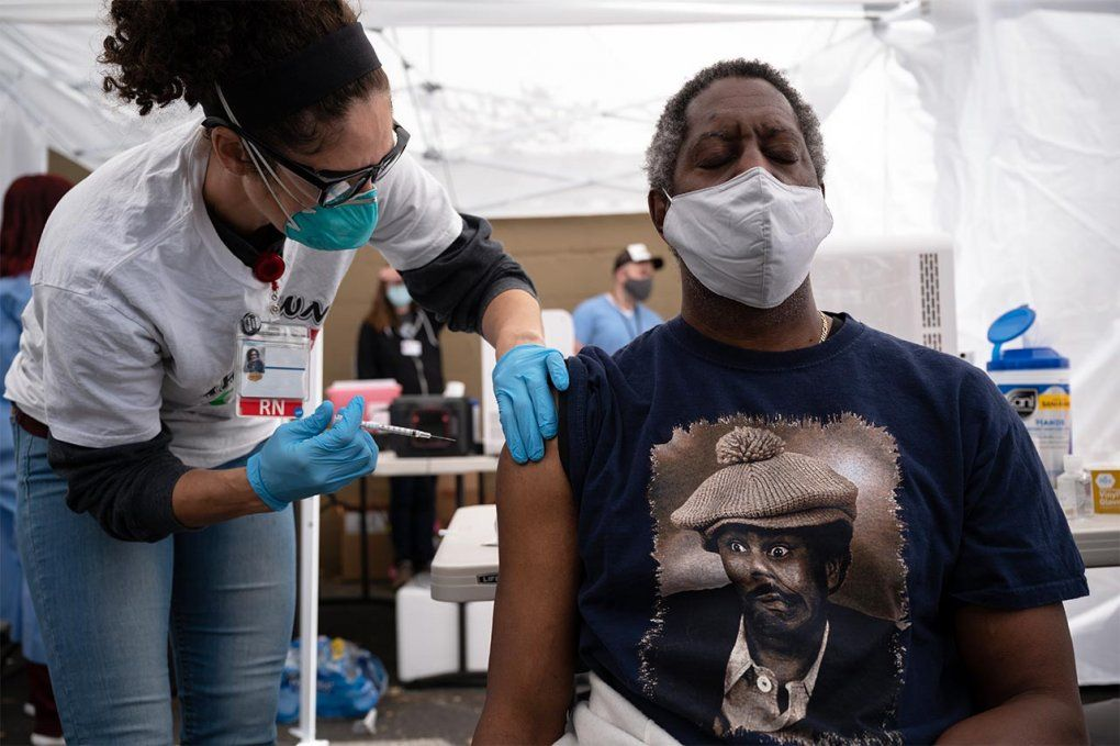 A Black man receiving a COVID-19 vaccine from a nurse at a community vaccine clinic.
