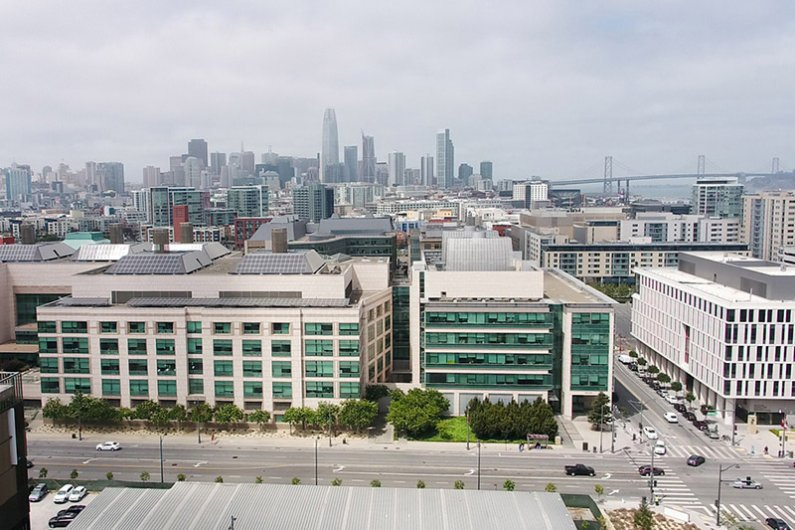 Aerial view of Mission Bay campus with San Francisco and the Bay Bridge in the distance