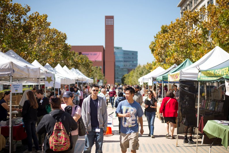 Two students walk through a farmer's market on the Mission Bay campus