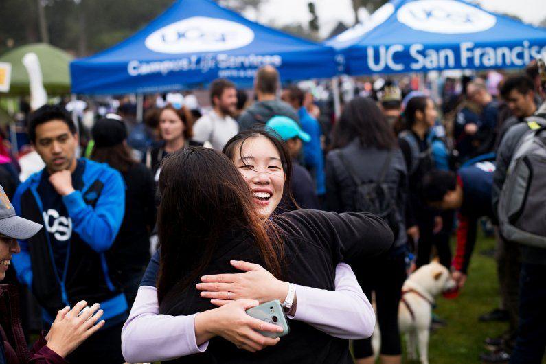 Women hugging at an outdoor event.