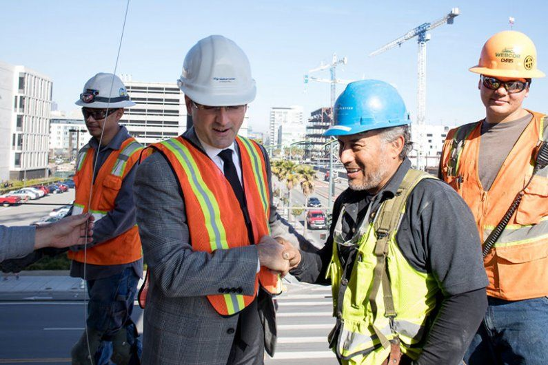 Men shaking hands at a construction site.