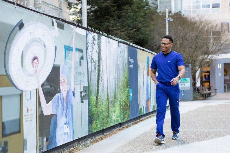 Man walking past branded construction fences.