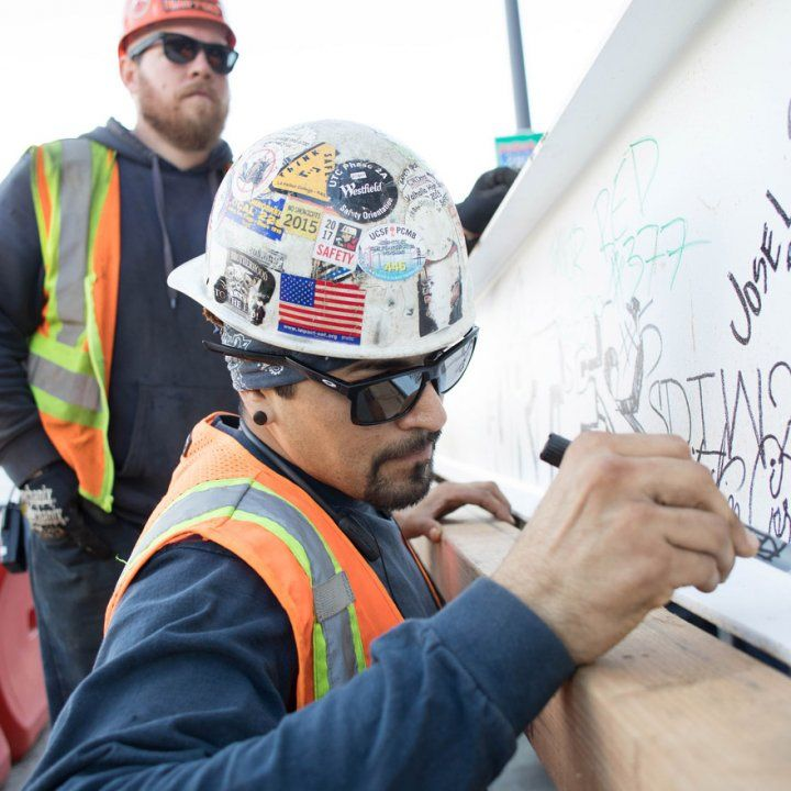 A construction worker signs the final steel beam of the Precision Cancer Medical Building before it is installed