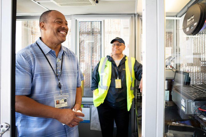 two workers stand in a parking garage