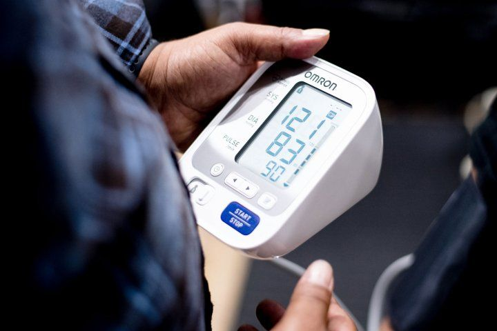 Hands holding blood pressure monitor