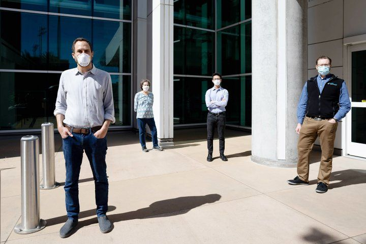 four researchers stand apart wearing face masks