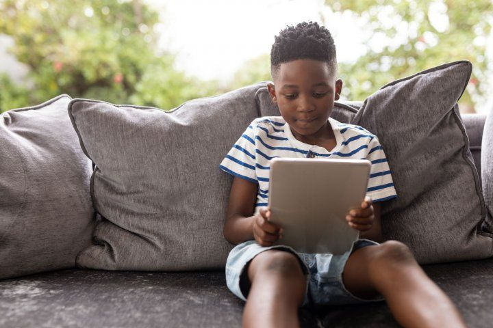 Boy sitting on couch using a tablet