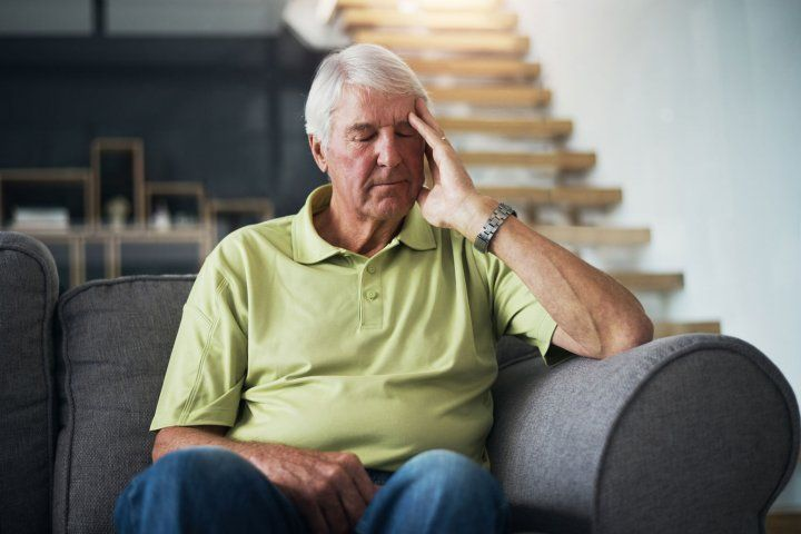 Elderly man sitting on couch with hand touching head