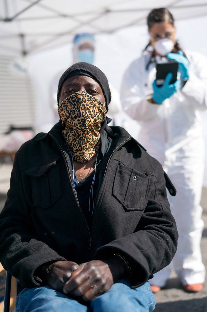 A Black man sits and waits in a leopard print handkerchief over his nose and mouth; a female health care worker in full body PPE works in the background.