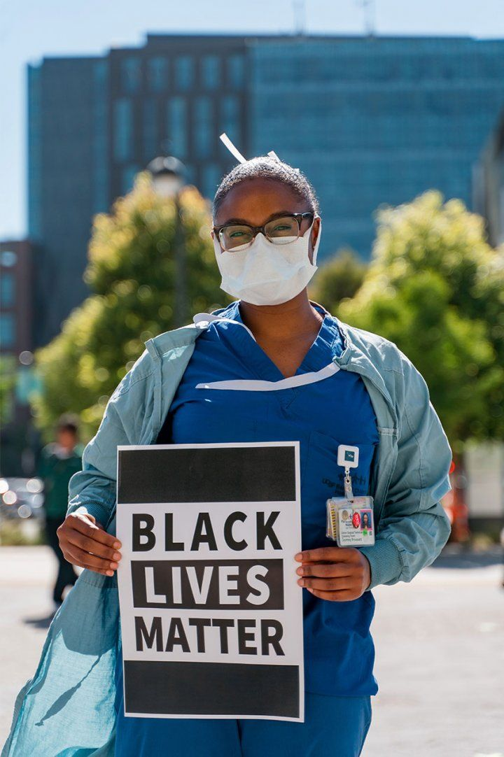 "A Black UCSF health care worker stands in front of UCSF Medical Center in scrubs and a face mask, holding a sign that reads ""Black Lives Matter."""