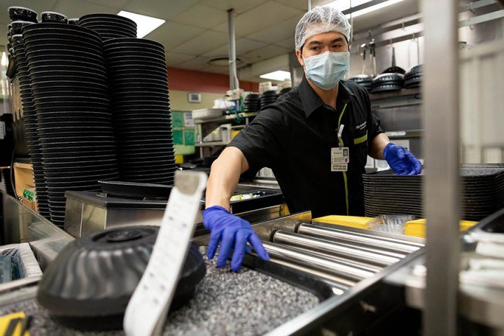 Food services worker grabs a tray while wearing protective gear