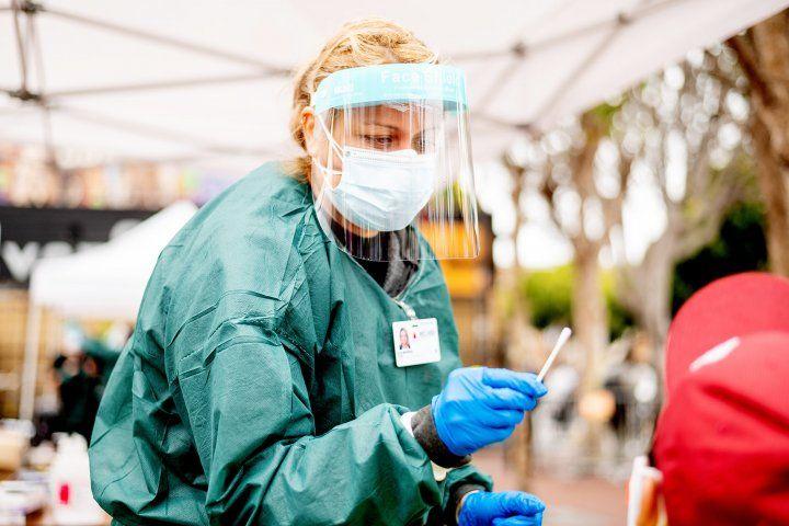 nurse administers a COVID test