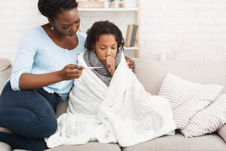 mother looks at thermometer with sick daughter