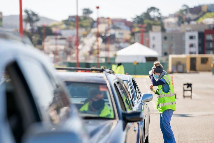 Cars lined up in parking lot with worker in neon yellow vest