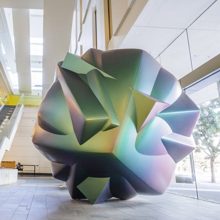 A multicolor multifaceted sculpture resembling a cell or microbe sits in the lobby