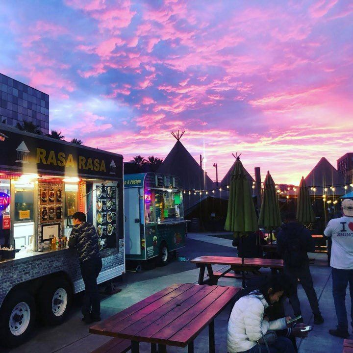A dramatic sunset lights up picnic tables and a row of food trucks