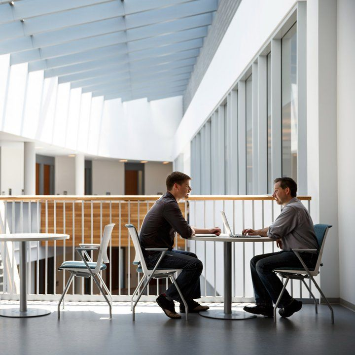 Two colleagues sit on a sunlit upper level balcony in the Sandler Neurosciences Center