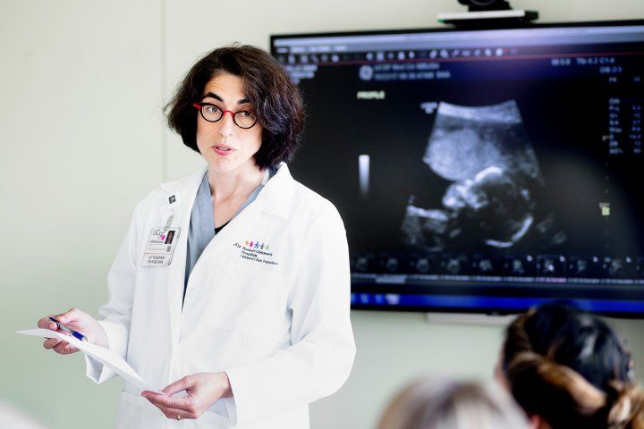 Tippi MacKenzie talks while an ultrasound image of a fetus is on a screen behind her