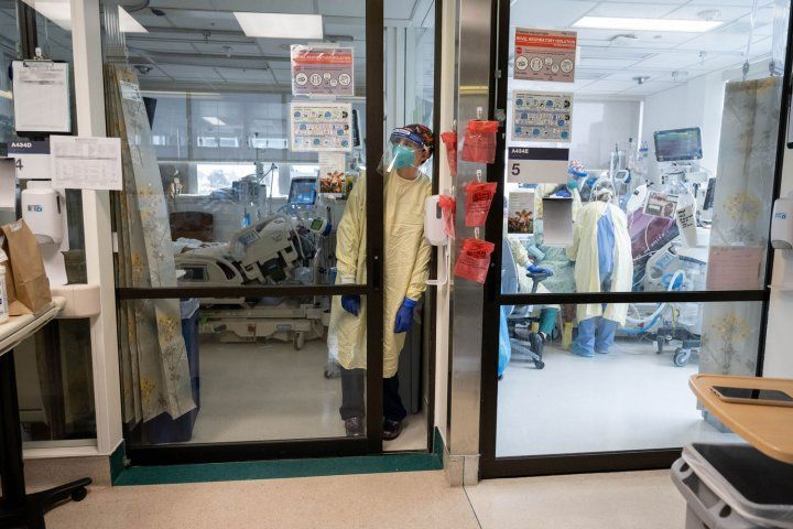 Nurse in PPE leaning against wall in ICU