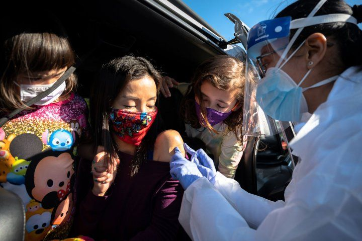 Woman with two children receiving a vaccine at a drive-through