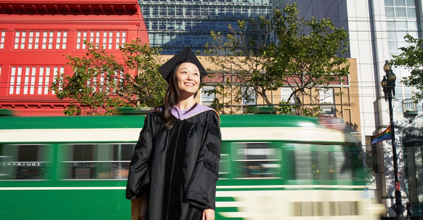 UCSF graduate standing on Market Street as streetcar goes by