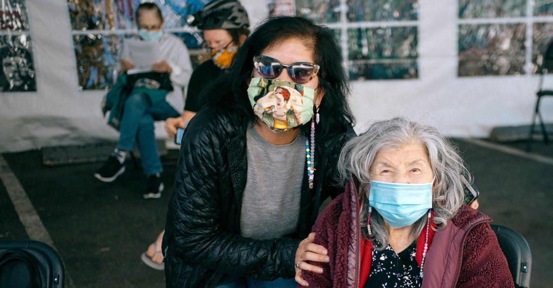 Zwei Frauen, eine Tochter und ihre ältere Mutter, tragen am 24. und Missionsstopp an einer von der UCSF betriebenen COVID-19-Impfstelle Masken