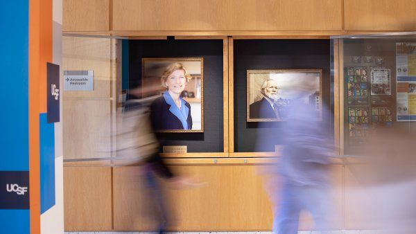 people walk by the portraits of Susan Desmond-Hellmann and Michael Bishop in the hallway of the Medical Sciences Building on Parnassus Heights campus