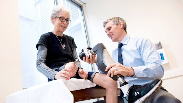 a doctor adjusts a prosthetic leg for a patient
