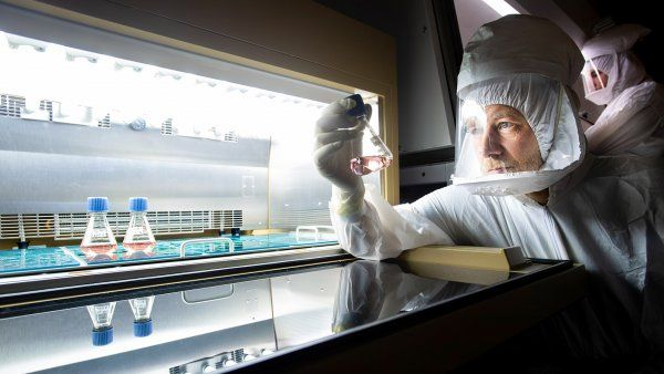 researcher in full-body protectionholds a sample in a lab