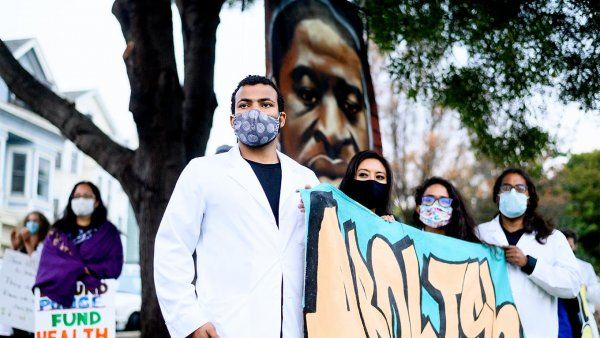 "UCSF Nurses gather in Oakland for a Black Health Matters protest; a male Black nurse in a white coat and face mask stands with female nurses, holding a sign that reads ""Abolish"" in graffiti style; a large mural of George Floyd's portrait is in the background."
