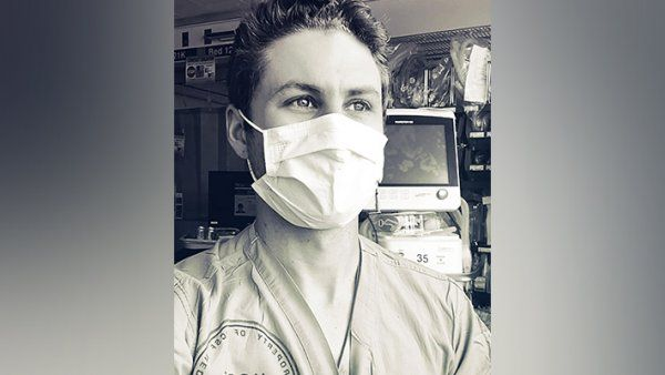 Portrait of Max Rausch in scrubs and a face mask at the hospital.