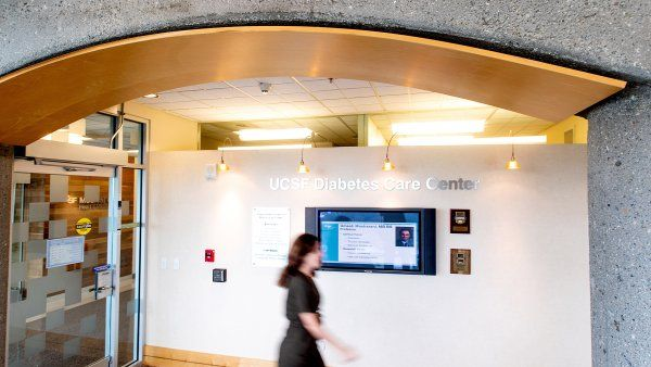 person walks by the sign of the UCSF Diabetets Care Center
