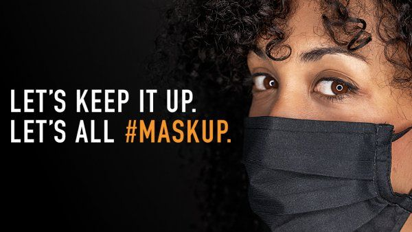 Woman wearing a face mask with text: Let's keep it up. Let's all #MaskUp