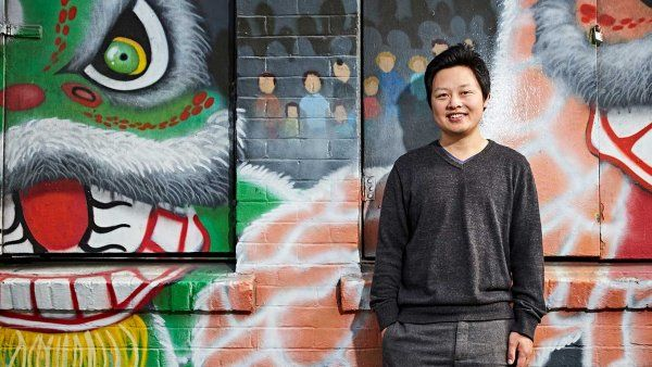 Photo of Richard Feng, MD, in front of a mural of painted dragons, in Chinatown, San Francisco.