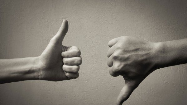 Black and white photo of one hand giving thumbs up, one hand giving thumbs down