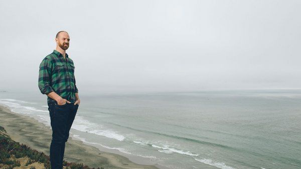 Matthew Wetschler, MD, stands on a sandy cliff overlooking the ocean.