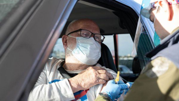 Older man in car about to receive a vaccine in his left arm