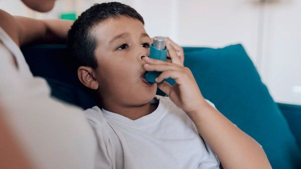 Child sitting on couch using an inhaler