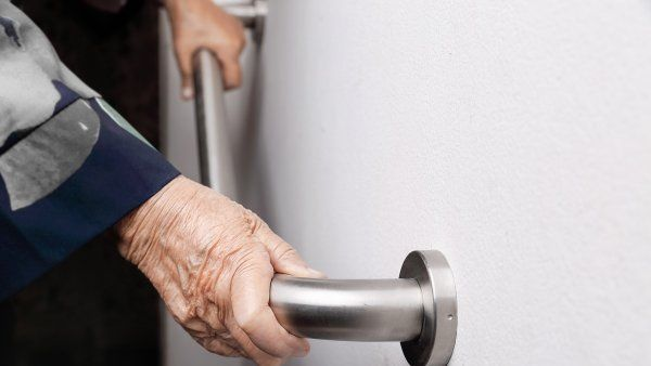 closeup of elderly hands holding a safety bar