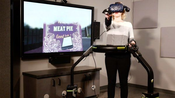 woman wears a VR headset while walking on a treadmill machine