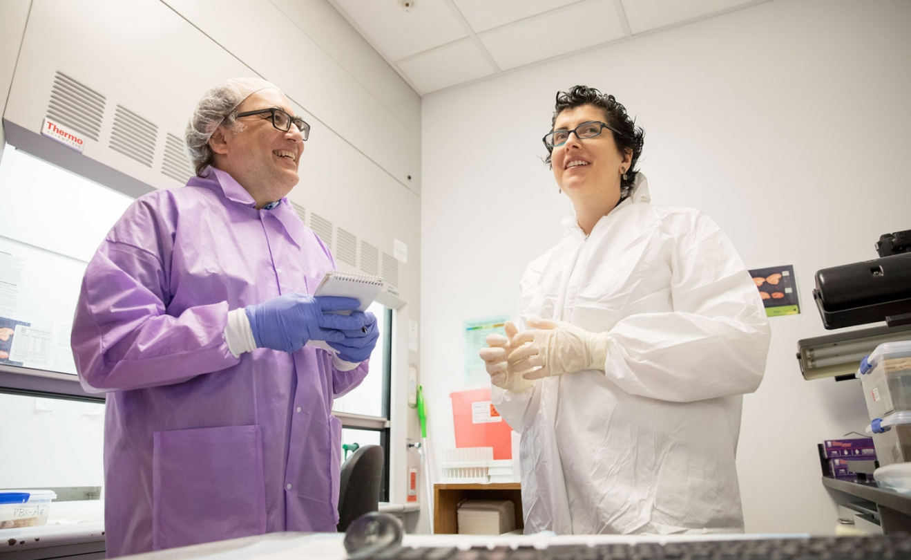 Josh Kornbluth talks with a researcher in a lab