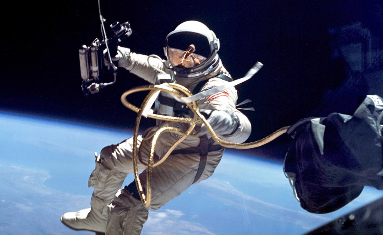 an astronaut on a spacewalk with Earth behind him