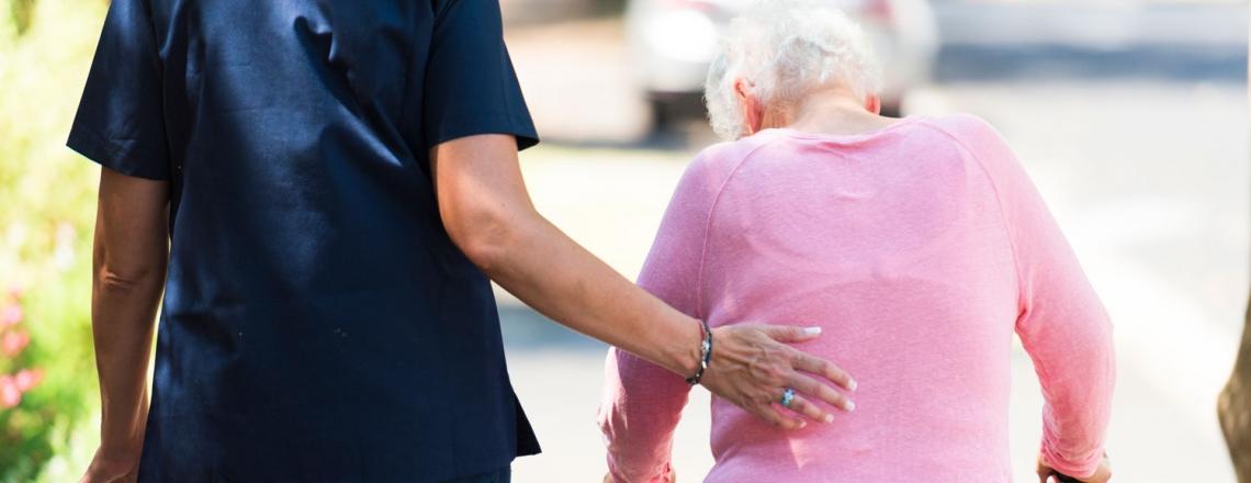 Care worker walking with elderly woman
