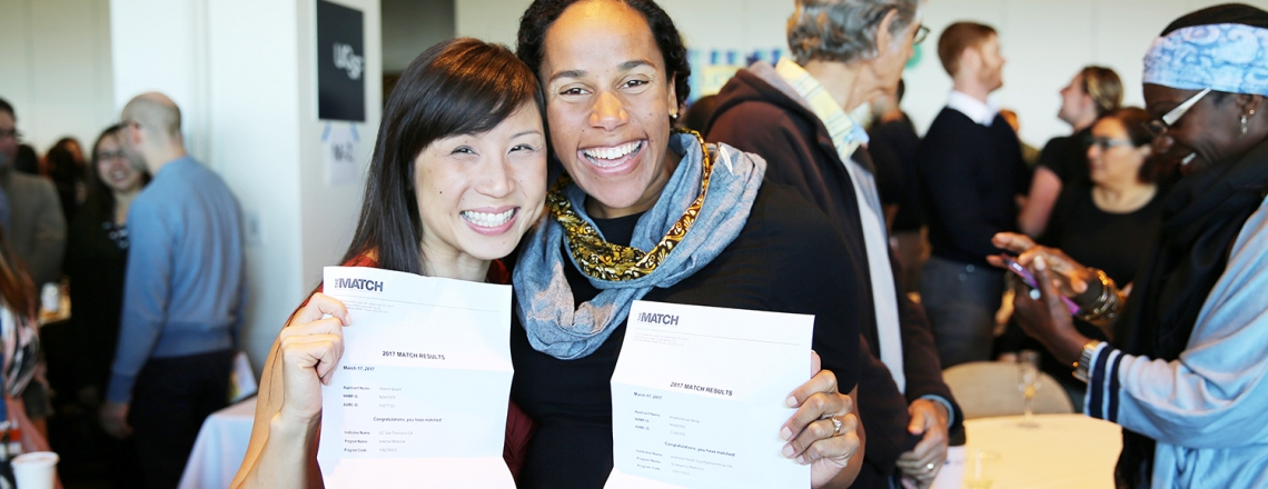 Two UCSF students hold up their match letters during the Match Day event