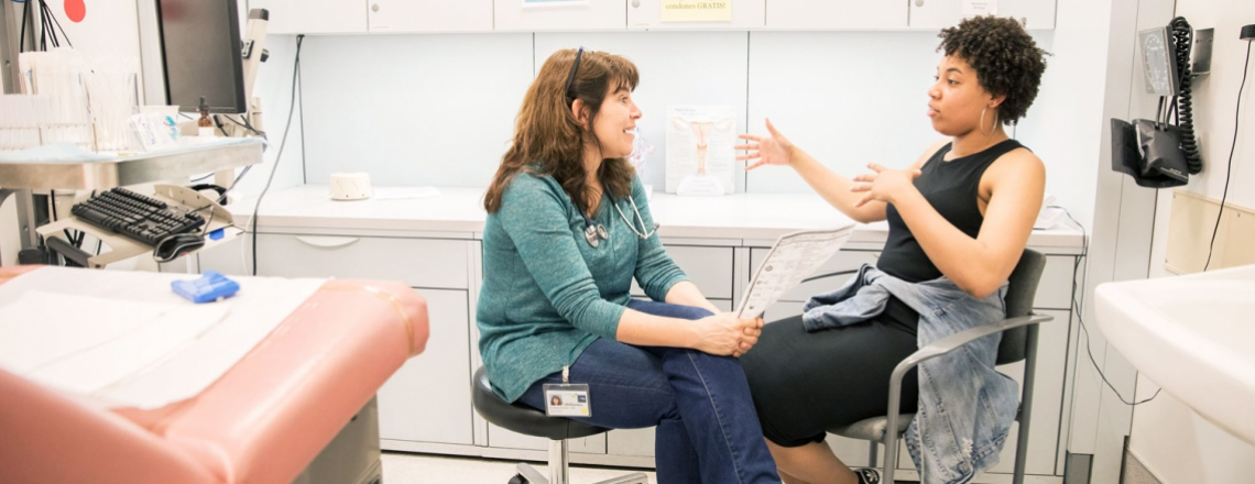 UCSF doctor talks to a patient in an exam room at New Generation Health Center