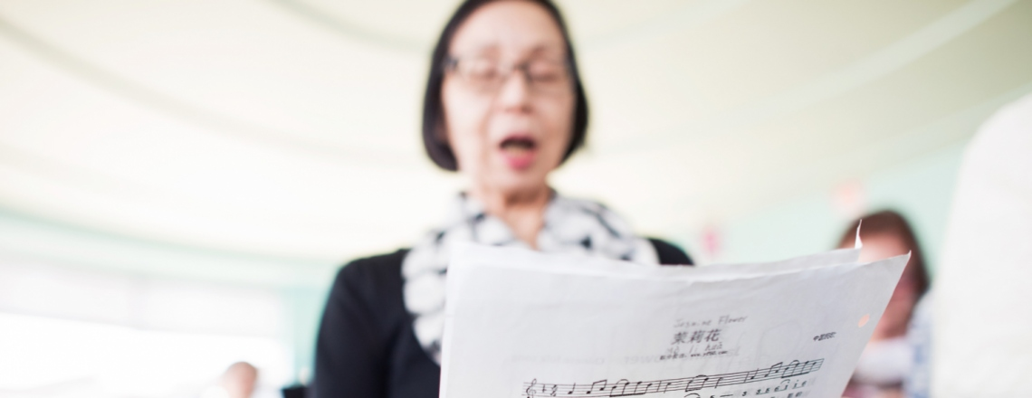 Woman holding and reading music sheet.