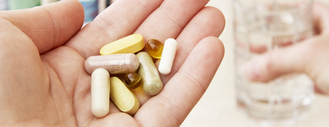 Handful of vitamin supplements.