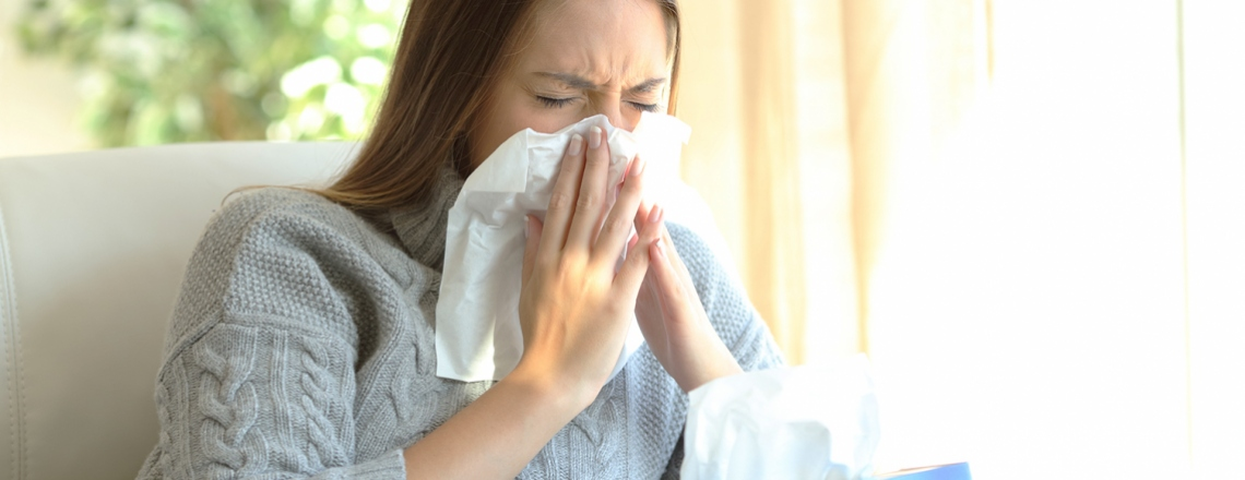 a sick woman blows her nose into a tissue